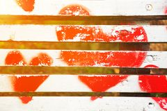 Red hearts painted on a white wooden bench. In Love concept with golden glow from the sun royalty free stock photo