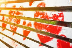 Red hearts painted on a white wooden bench. In diagonal view with golden glow from the sun. Love concept royalty free stock photography