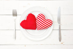Red hearts on plate, fork and knife Stock Image