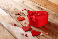 Red hearts and present box on wooden table Royalty Free Stock Photos