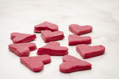 Red hearts of raw beet dough on a white table, side view Stock Images