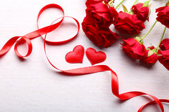 Red hearts, ribbon and beautiful roses on wooden table Royalty Free Stock Images