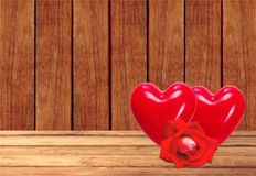 Red hearts and rose on wooden table over wooden planks backgroun Royalty Free Stock Images