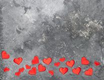 Red hearts are scattered on a gray textured background. Flat layout. Copy space stock photography