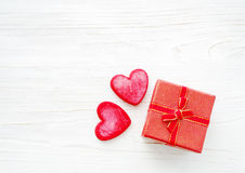 Red hearts and small gift box with a bow on a wooden white background. Royalty Free Stock Image