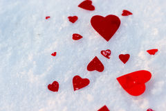 Red hearts on snow. Background Stock Photos