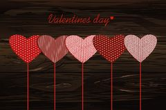 Red hearts on a stick with the image. Valentine`s Day. Vector il. Lustration. Greeting card with empty space for the label or advertising. On a wooden background Stock Photos