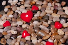 Red Hearts and Stones. Red stone hearts and polished rocks royalty free stock images