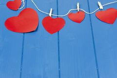 Red hearts on a string on a blue background Stock Photo