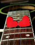Red hearts on the strings of a guitar. Hearts are a symbol of love. Valentine`s Day. Strings of the heart. Red hearts on the strings of a guitar. Hearts are a stock image