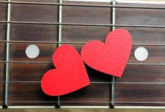 Red hearts on the strings of a guitar. Hearts are a symbol of love. Valentine`s Day. Strings of the heart Royalty Free Stock Photos