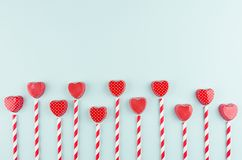 Red hearts and striped straws with copy space on trendy color mint backdrop as playful modern valentine`s day background. Red hearts and striped straws with stock photo