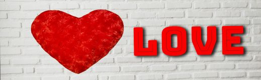 Red hearts and text love on white brick wall background For Valentine`s Day, banner horizontal for web and headline.  royalty free stock image