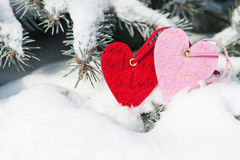 Red hearts toy in snowfall on fir tree Stock Photography