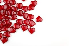 Red hearts on white background with copyspace. A lot of small red clear crystal shiny Valentine hearts on white background top view with copyspace Royalty Free Stock Photography