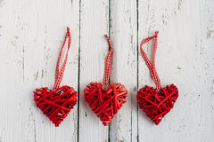 Red hearts on a white background. Red hearts made of wicker handmade on white background Stock Photos