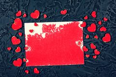 Red hearts and white blank sheet of paper on a black stone background. Valentine`s Day, Mother`s Day. Royalty Free Stock Photography