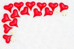 Red hearts on white fabric and rose buds background. Red hearts on white textured fabric background and rose buds with copy space for your message royalty free stock photography