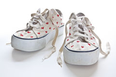 Red hearts on white sneakers Stock Photos
