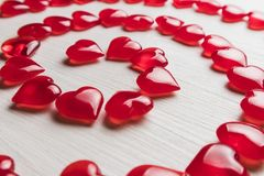 Red hearts on a white wooden substrate. Background of red hearts on a white wooden substrate Stock Image