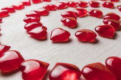 Red hearts on a white wooden substrate. Background of red hearts on a white wooden substrate Royalty Free Stock Photo