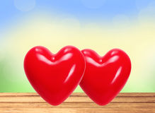 Red hearts on wooden table over nature Stock Image