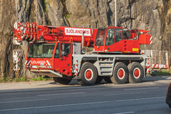 Red heavy mobile crane on a roadside Royalty Free Stock Photography
