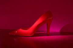 Red Heel. Single red shoe sitting alone in a purplish spotlight Stock Images