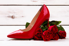 Red heel shoe and roses. Flowers and footwear on wood.. Gift with taste Royalty Free Stock Photos
