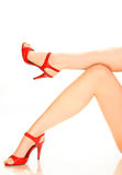 Red Heels. Female legs and red heels against a white back drop Royalty Free Stock Photography