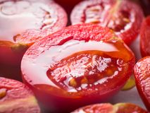 Red heirloom tomatoes with olive oil. Red heirloom tomatoes ready to be baked with olive oil royalty free stock image