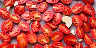 Red heirloom tomatoes with olive oil. Red heirloom tomatoes ready to be baked with olive oil royalty free stock photo