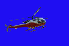Red helicopter. A swiss helicopter (model allouette II), isolated on blue Stock Photos