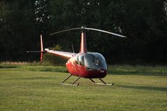 Red helicopter. To green runway at sunset Royalty Free Stock Photography