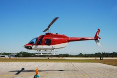 Red helicopter above ground Royalty Free Stock Images