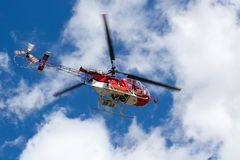 Red helicopter on the blue sky. (italian Alps royalty free stock photo