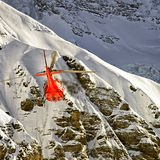 Red helicopter in flight in winter alps Royalty Free Stock Images