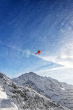 Red helicopter in flight in winter alps with snow powder streams Stock Images