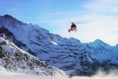 Red helicopter fly at Swiss Alps mountains Maennlichen winter stock photo