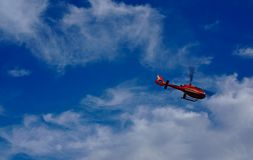 Red helicopter flying with blue sky and white clouds in background royalty free stock image