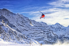 Red helicopter flying at swiss alps near Jungfrau mountain. In winter Stock Photography