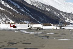 A red helicopter, a fuel truck and a private jet in the airport of St Moritz in the snowy alps switzerland in winter Stock Photo