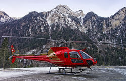 Red helicopter in heliport at swiss alps Royalty Free Stock Image