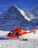 Red helicopter landed near alpine peak near Jungfrau mountain Royalty Free Stock Photos