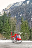Red helicopter landed at swiss alpine heliport Stock Photo