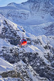 Red helicopter landing at swiss alps near Jungfrau mountain Stock Photos