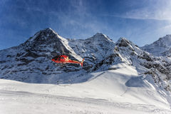 Red helicopter landing at swiss ski resort near Jungfrau mountai Stock Photography