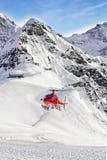 Red helicopter landing at swiss ski resort near Tschuggen peak Royalty Free Stock Images