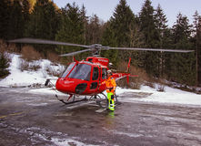 Red helicopter and serviceman at Gsteigwiler heliport Royalty Free Stock Photography