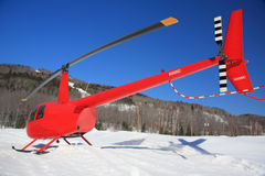 Red helicopter in snow Stock Photo